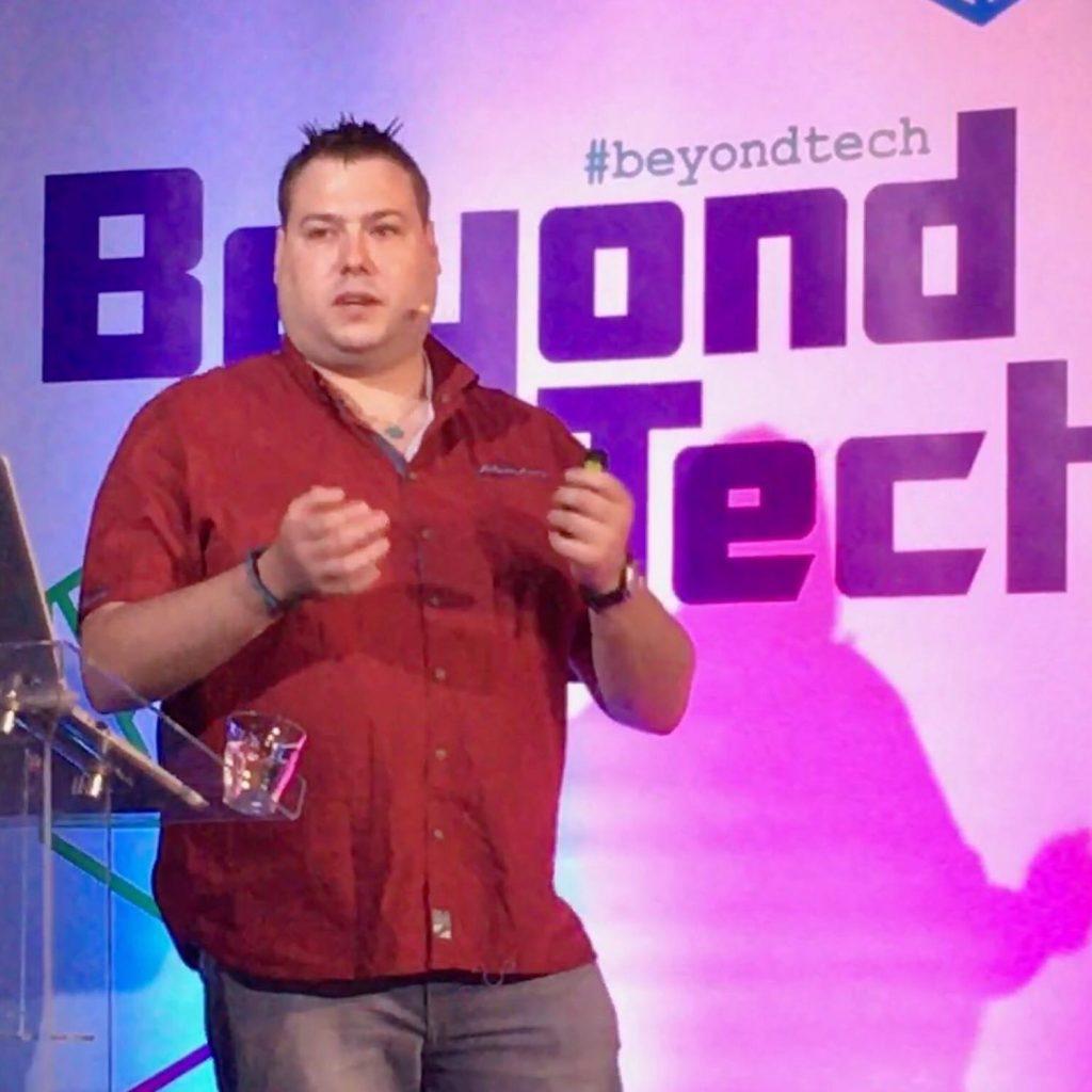 Foto van Dennie die aan het spreken is op een conferentie.