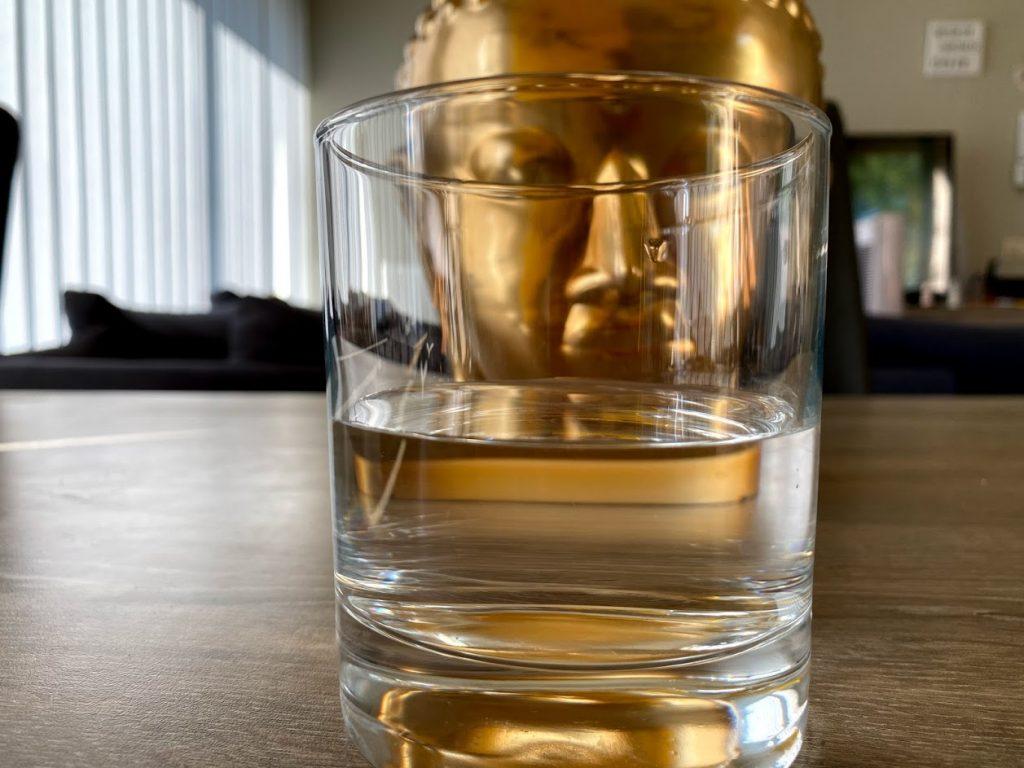 Foto van Buddha beeldje met een half vol glas.